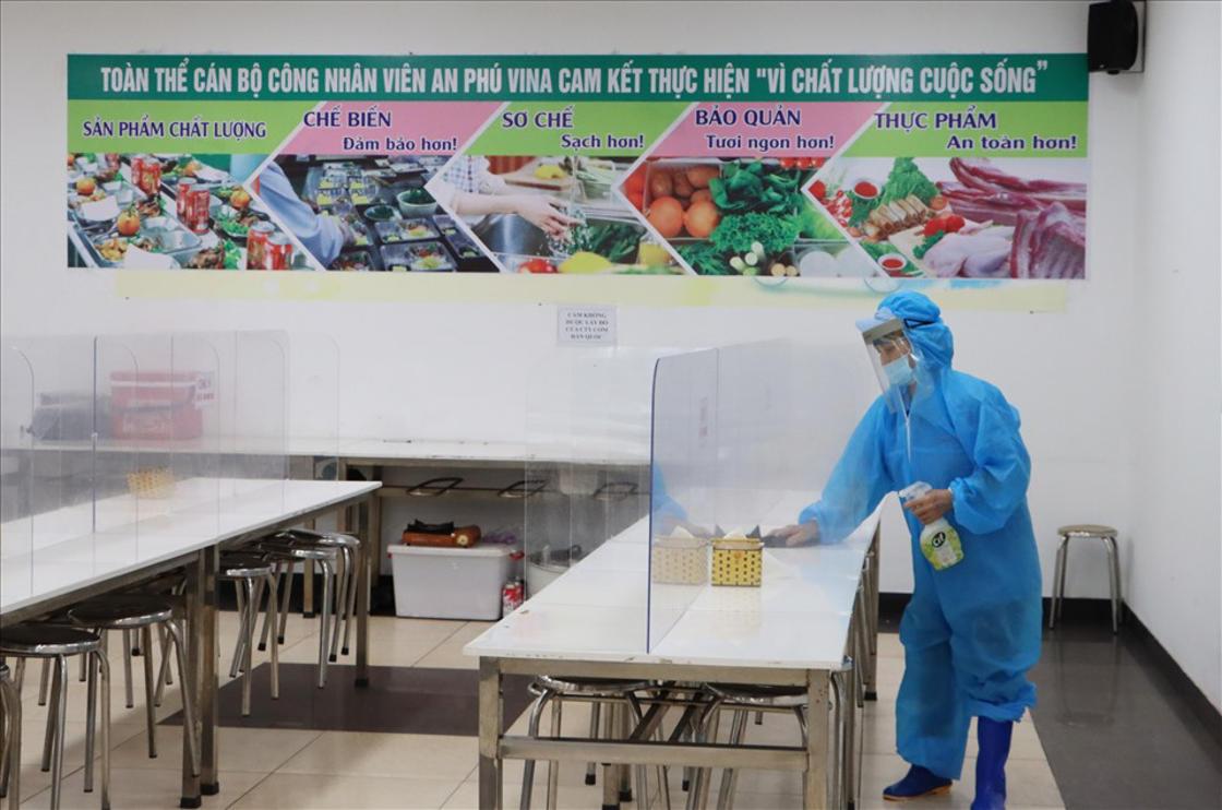 Nhân viên nhà bếp tiến hành vệ sinh khử khuẩn tại khu vực nhà ăn của 1 doanh nghiệp trong KCN Quế Võ. Ảnh: PV.